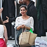 Kim Kardashian carried her bag as Kanye West gave someone a handshake.