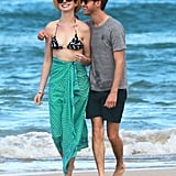 Anne Hathaway and Adam Shulman grinned as they strolled a beach in Oahu, HI.