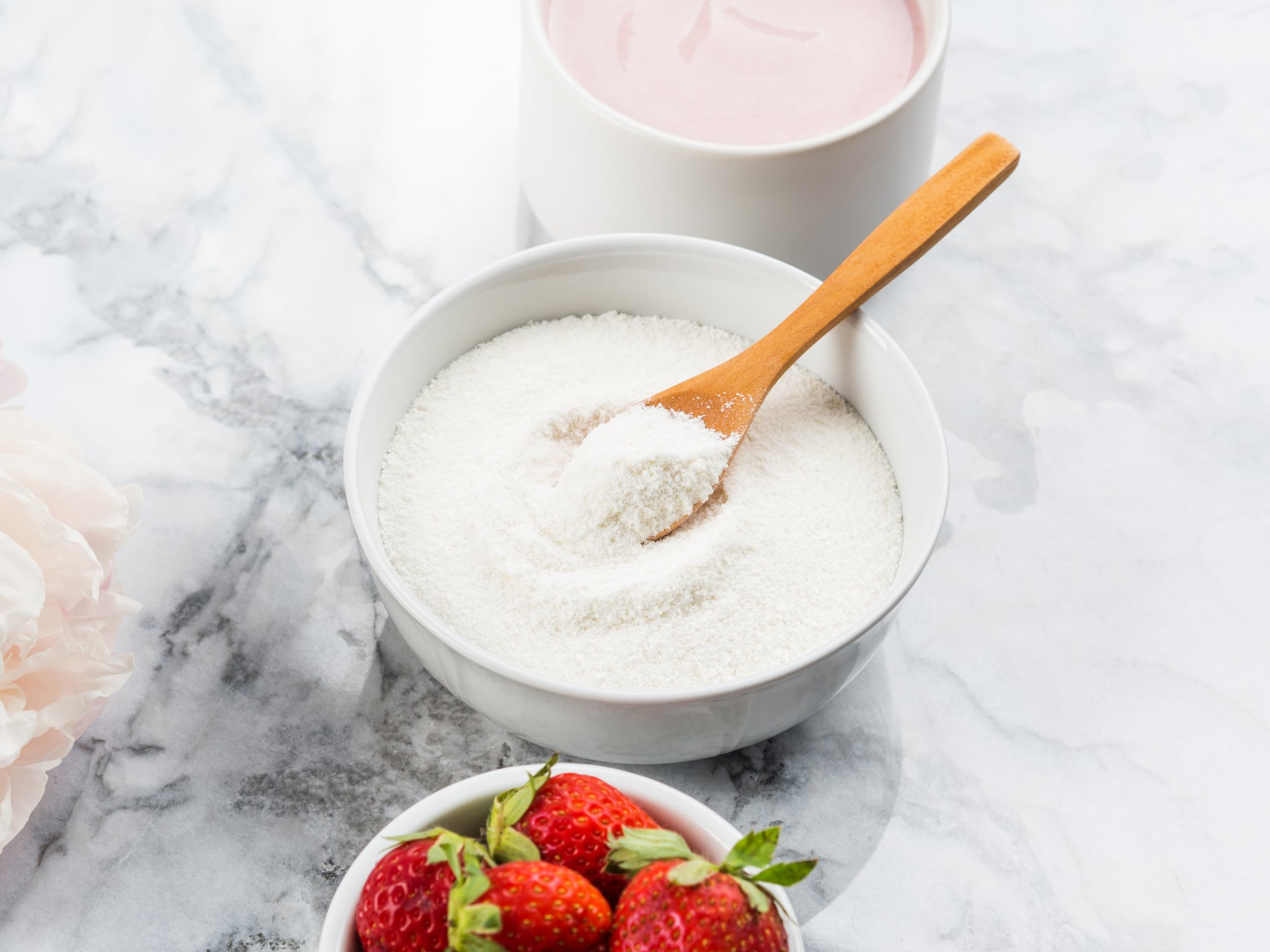 Collagen protein powder in bowl with wooden spoon on marble table. Adding collagen supplement to strawberry yogurt. Angle view
