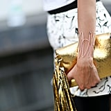 A wire bracelet plays up this fringe-embellished clutch in the most subtle, perfect way.