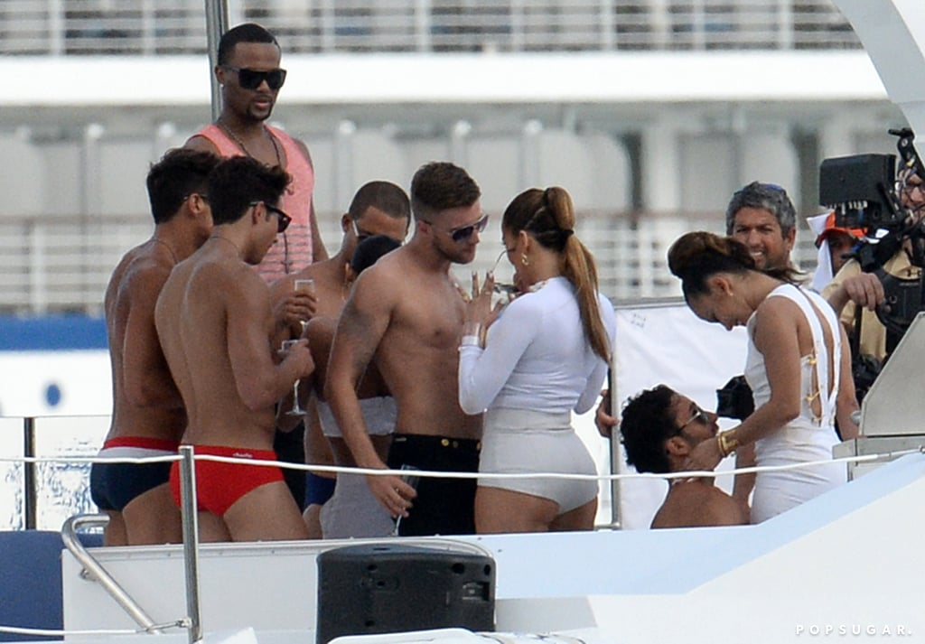 """Jennifer Lopez looked like she was hard at work when she filmed scenes for her a music video in Miami on Wednesday while surrounded by a group of hunky, bronzed men. The singer wore white hot pants while she danced on a yacht with the gaggle of guys and got very close to one handsome actor in particular. However, it was all for the cameras, as J Lo's boyfriend, Casper Smart, was also on the set, watching his loved one work her magic. Jennifer has been filming the new video clip over the past few days, even transforming one Florida street into a mini-Carnival parade for a festive scene with Pitbull. The new video is for """"We Are One,"""" the official anthem for the FIFA World Cup, which will take place in Sao Paulo, Brazil, in June. World Cup songs can turn into big hits for stars, as Shakira's """"Waka Waka"""" anthem for the 2010 competition in South Africa became a massive hit on the pop charts."""
