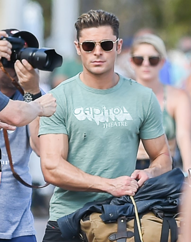"""Zac Efron was spotted on the set of Baywatch in Boca Raton, FL, on Monday, looking like his usual hot self. The actor showed off his bulging biceps in a green t-shirt while filming on the street, where, naturally, onlookers stopped to get a glimpse of the handsome star. That same day, Zac uploaded a photo of his character Brody on Instagram, writing, """"Meet Brody. Cruising into The Bay with nothing to his name but a duffle bag and a bike #Baywatch.""""  Zac's costar Dwayne Johnson has also been hard at work. Just last week, Dwayne brought his signature charm and muscular physique to the set, where he was seen shooting a rescue scene with Zac and their costar Ilfenesh Hadera. Read on to see more of Zac and his insane muscles, and then see how much he's changed in the past decade."""