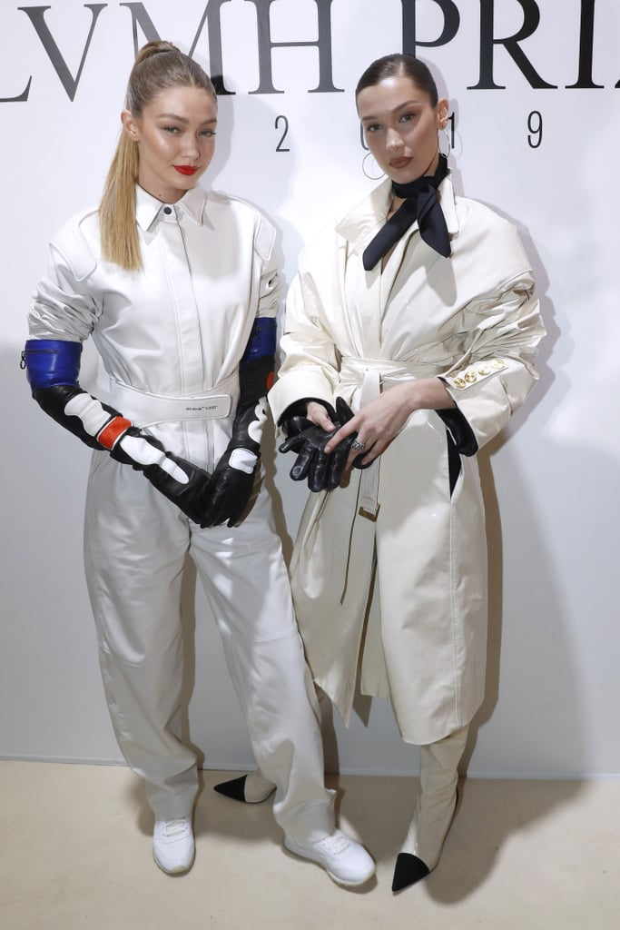 Gigi and Bella Hadid showed up to the Louis Vuitton party in Paris on March 1 wearing complementary outfits, because stylish minds think alike. The sisters flaunted their own fashion choices in unique ways but matched where it counts: with their bold statement gloves.  While Gigi opted for a white jumpsuit from Off-White's Fall 2019 collection, Bella chose a patent trench coat, which gave off a similar silhouette to her sister's look when cinched at the waist. Gigi paired her sporty ensemble with sneakers and a bold red lip, while Bella added some Parisian flair with pointed black colour-blocked boots and a neckerchief. The highlight of both their outfits had to be the black gloves they wore — slightly different, but equally dramatic. Read on to see more snaps of their looks.       Related:                                                                                                           Gigi Hadid's Prada Mini Dress Is Made For Partying in Paris