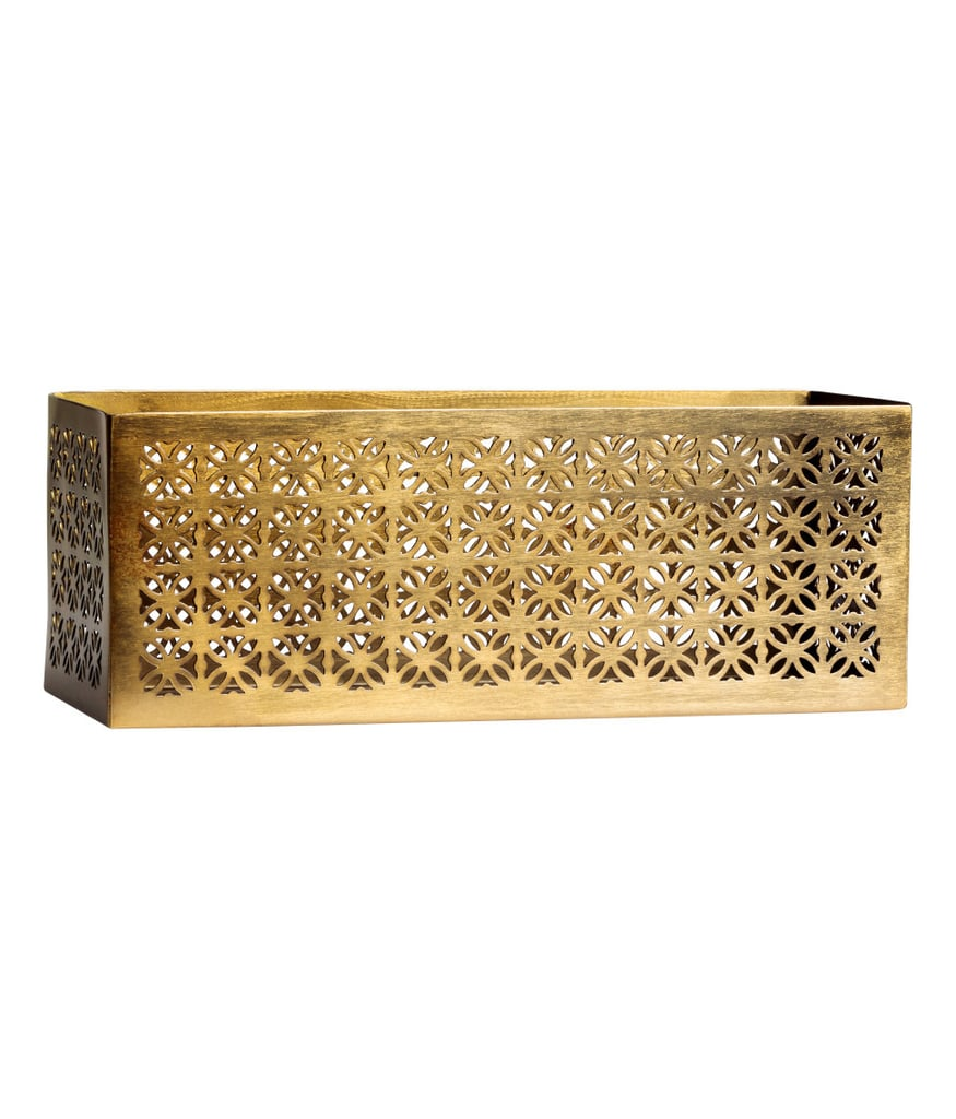 Corral disparate remote controls, coasters, and other coffee table items in a decorative container, like this metal storage box ($25).