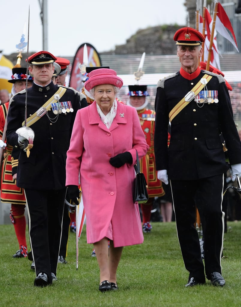 Hours after the Duchess of Cambridge gave birth to the new royal baby, a girl, Queen Elizabeth II made an appearance wearing all pink. She had a big smile on her face during the official engagement in Richmond, England, where she watched the amalgamation parade of The Queen's Royal Lancers before speaking to soldiers and their families. Meanwhile, her grandson Prince William was busy introducing his baby girl to the world alongside his wife. Keep reading for more pictures of the queen's appearance, then see the first photos of the new royal baby plus adorable snaps of Prince George at the hospital!