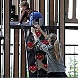 Gisele Bundchen helped Benjamin Brady up a climbing wall on a playground.