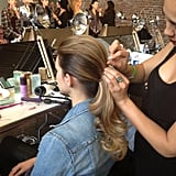 The next step: divide the hair into two sections — a smaller portion between the temples and a larger bottom part. The bottom section was secured into a low ponytail. Then the top piece was combed over the and held with bobby pins. A bride could transition back to this double ponytail look easily before the wedding reception.