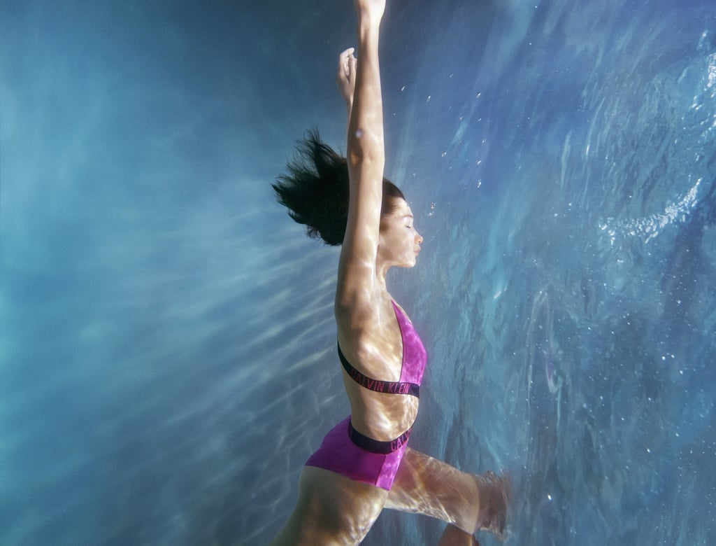 "Bella Hadid dives to new depths in Calvin Klein's dreamy underwater swimwear campaign. ""Heaven to be able to work in the water,"" the model wrote on Instagram referencing her pre-COVID photoshoot from ""almost a year ago"" — back when it was the norm to scout locations and enlist the help of massive teams. Nowadays, at-home photoshoots are more typical, but that won't stop us from admiring Calvin Klein's latest designs.  Bella joined models Conor Fay, Malika El Masiouhi and Solange van Doorn at a home in upstate New York to show off the bold swimwear selections for photographer Charlotte Wales. The collection includes standout logo banding along each playful suit, while still maintaining their classic styling. The brand told POPSUGAR that Bella ""loved all of the brightly colored neon pieces,"" so we wouldn't be surprised if she kept a few for herself. Check out the campaign ahead to get a closer look for yourself.       Related:                                                                                                           Jasmine Sanders on Her Sports Illustrated Cover, Diversity in the Industry, and Her Newfound Confidence"
