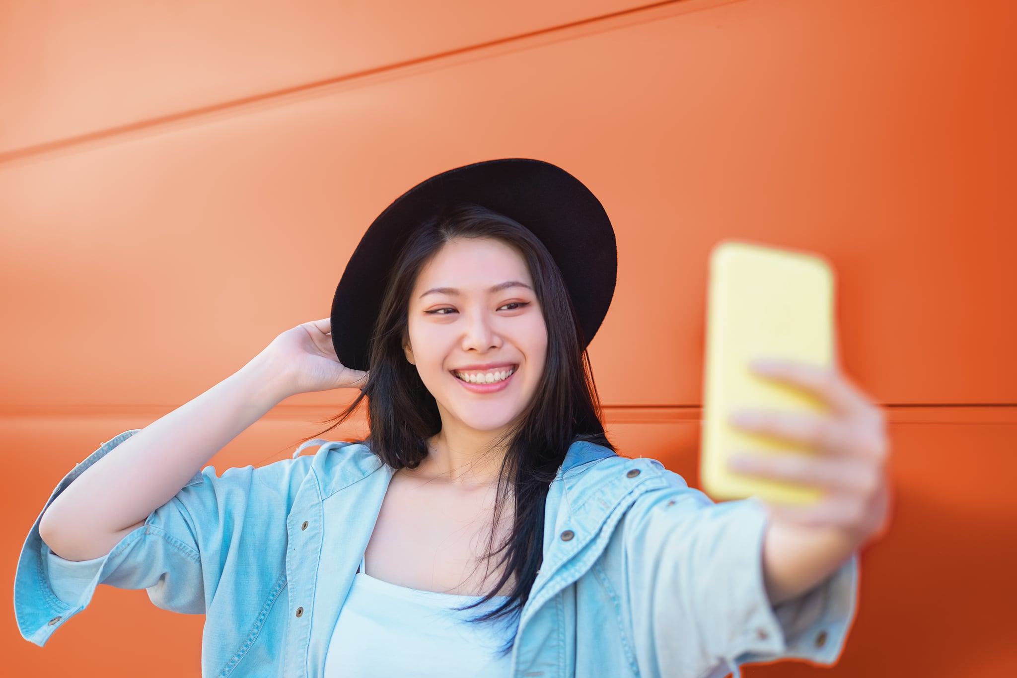 Happy Asian girl taking selfie with mobile smart phone outdoor - Trendy influencer having fun with new trends social networks apps - Millennial generation lifestyle people addicted technology