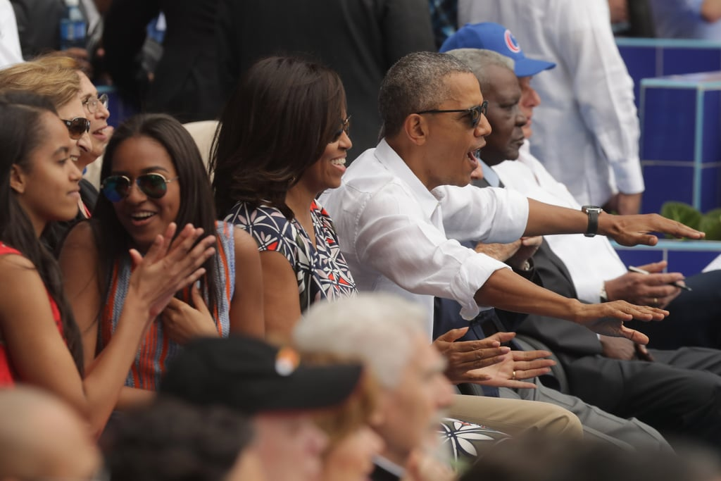 The Obama family just keeps bringing it! Just days after arriving in Cuba, President Obama, Michelle, who stunned in a gorgeous Tory Burch dress, and daughters Sasha and Malia all attended a baseball game between the Tampa Bay Rays and the Cuban national team in Havana on Tuesday. Of course the brood was there to watch the game, but it was their cute antics that ended up stealing the show. At one point, President Obama was caught playfully pushing Michelle's arm and was even spotted doing the wave with Cuban President Raul Castro. The three-day trip marks the first time that an American sitting president has visited the country in almost 90 years. Keep reading to see more photos of the fun outing, and then look back at Sasha and Malia's sweetest moments of all time.