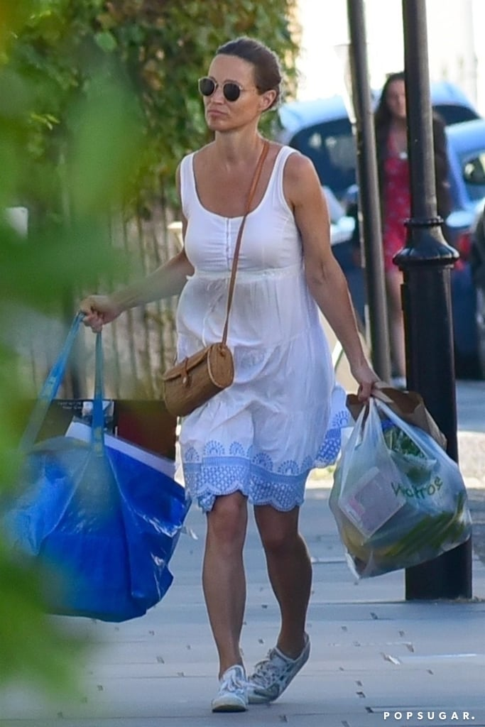 Pippa Middleton is living it up with her maternity style. A few weeks ago she was spotted in a $158 pink J.Crew dress, and now she's wearing something completely different and equally adorable. The mother-to-be was captured wearing a simple white dress with an intricate blue pattern at the bottom. She paired the dress with a straw bag, white sneakers and round sunglasses. Doesn't the pattern kind of you remind of the lace on Pippa's wedding dress? This outfit is perfect to rock while out shopping, like Pippa did, because it's airy, simple and perfect for the hot weather. Keep scrolling to get a closer look and shop similar options ahead.      Related:                                                                                                           16 Times Duchess Kate and Pippa Middleton Dressed So Similarly, We Had to Do a Double Take