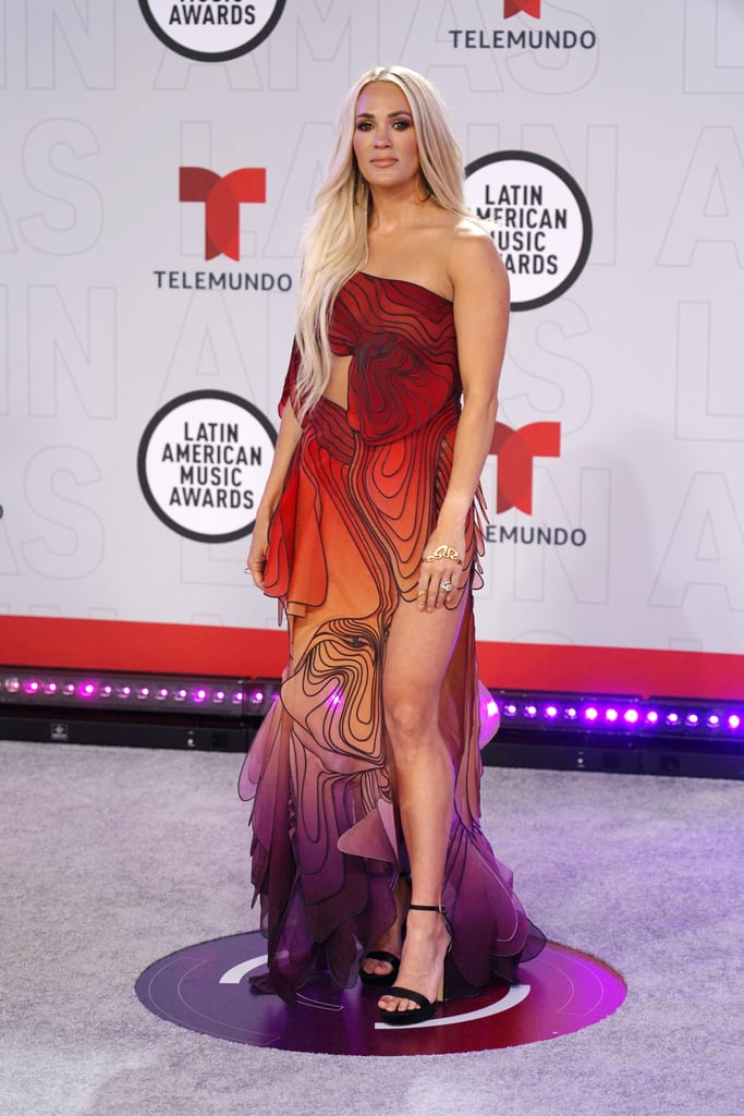 "Carrie Underwood was a walking work of art at the 2021 Latin American Music Awards. The singer, who performed ""Tears of Gold"" with David Bisbal at the award show on Thursday, wore what is likely one of her most daring red carpet looks to date: a delicate gown resembling a monarch butterfly by Iris van Herpen. The dress is a definite departure from the princess ball gowns and beaded minidresses Carrie typically gravitates toward. The Dutch fashion designer is known for her advanced techniques and early adoption of 3D printing as a method of construction. She notably interned at Alexander McQueen before launching her own label in 2007. Carrie let the artful dress have the spotlight by keeping her accessories simple, wearing black sandals, gold hoop earrings, and a gold bracelet. Take a closer look at the adventurous outfit ahead.      Related:                                                                                                           20 Bridgerton-Inspired Gowns That Are Perfect For Your Regencycore Wedding"