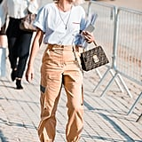 An embroidered tee feels cool yet polished when tucked into utilitarian trousers with pointed-toe pumps and a logo bag.