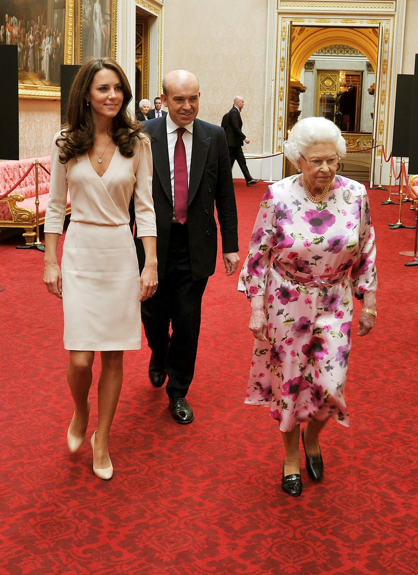 Kate Middleton and Queen Elizabeth walking in Buckingham Palace.