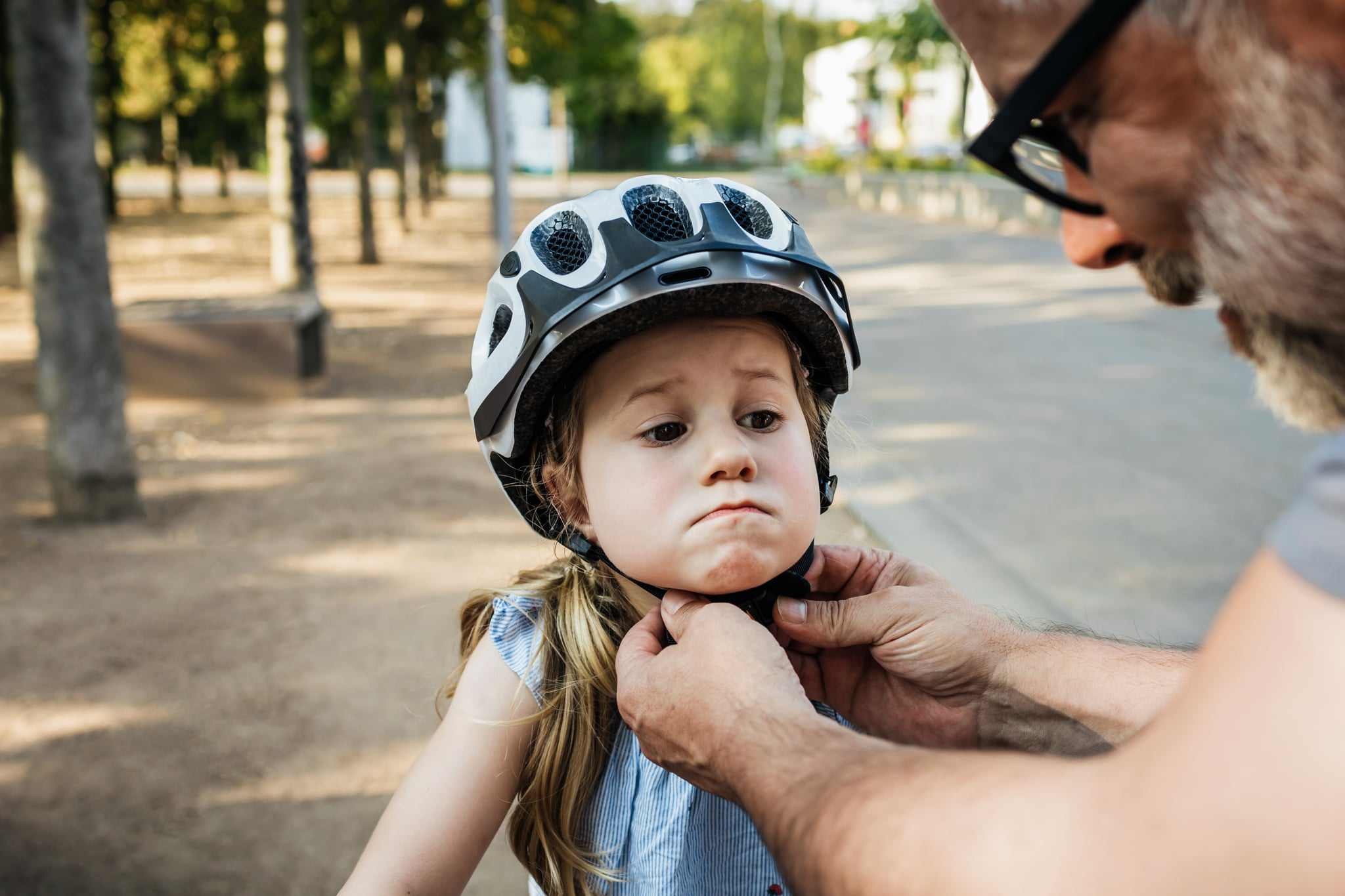A grandpa carefully doing up his granddaughters crash helmet while on a day out at the park together.
