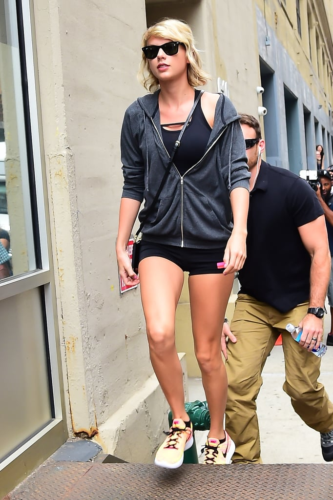"Another day, another photo of Taylor Swift that makes us want to take on one of those 30-day squat challenges. Now that the fallout from her mid-July feud with Kim Kardashian and Kanye West has died down, the ""New Romantics"" singer has been spotted out and about all over NYC lately, from heading to the gym to walking around the city sporting curly hair from her Fearless days. On Wednesday, Taylor spent a rainy afternoon in the Chelsea neighbourhood of NYC going to the gym while flaunting her mile-long legs in a pair of itty-bitty shorts that had us especially in awe. She's definitely no stranger to showing off her $40 million legs, which she did a few times while frolicking around Europe with boyfriend Tom Hiddleston earlier this Summer. Check out more photos from Taylor's outing!"