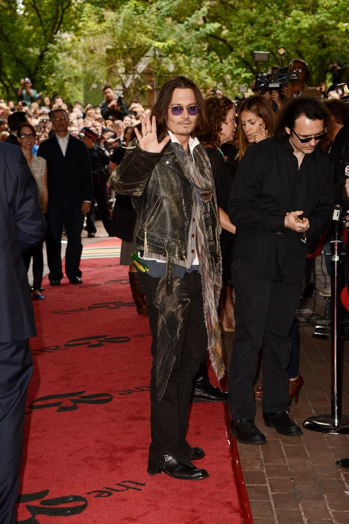 "Johnny Depp waved to the crowd at the Toronto International Film Festival yesterday. He was there supporting West of Memphis, which examines the case of three men later named the ""West Memphis Three,"" who were wrongly convicted of homicide and finally let out of prison last year after 18 years behind bars. Johnny, along with the Dixie Chicks' Natalie Maines and Eddie Vedder, was among the stars who helped pay the legal fees to free the men. Johnny has become close with one of the accused, Damien Echols, and the duo apparently share matching tattoos. Johnny revealed during a press conference yesterday that the ink on the right side of his chest was designed by Damien and is ""one of my all-time favorites, and it means quite a lot to me."""