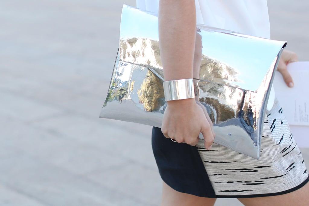 A mirrored metallic clutch mirrored a sleek cuff.