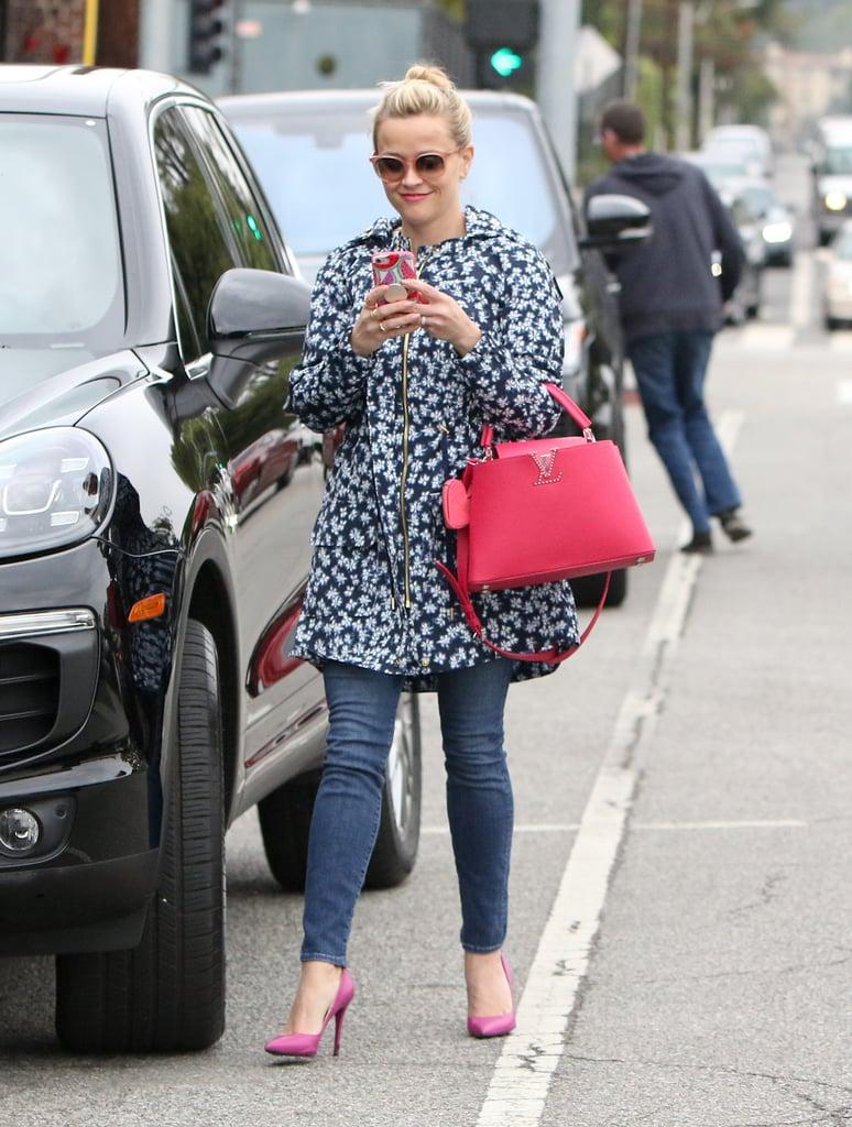 Wearing a floral print jacket, skinny jeans, and hot-pink handbag.