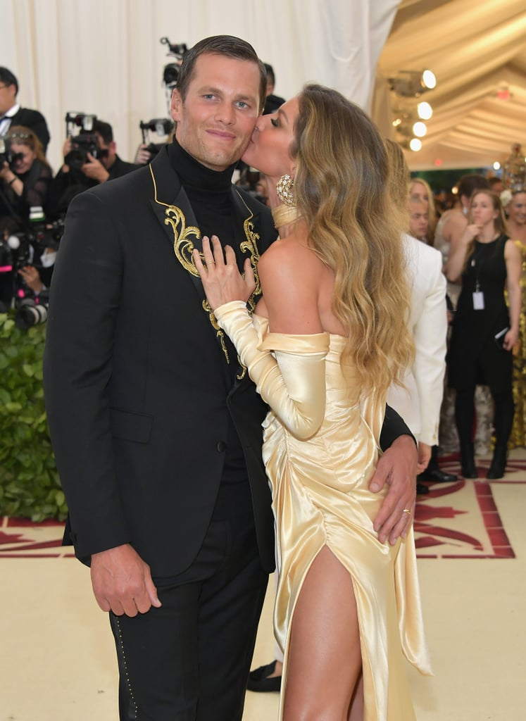 Celebrity couples are known for turning the Met Gala into their own personal date night, but none of them do it quite like Gisele Bündchen and Tom Brady — and this year was no different. On Monday, the couple steamed up the star-studded event, as per usual, when they arrived in matching Versace ensembles. Gisele let her hair down and wore a gold dress with a thigh-high slit and Tom donned a black suit with a turtleneck. The pair played up their PDA while posing for the cameras, and honestly, it should be a sin for them to look this good. Read on to see more of their sexy night out!