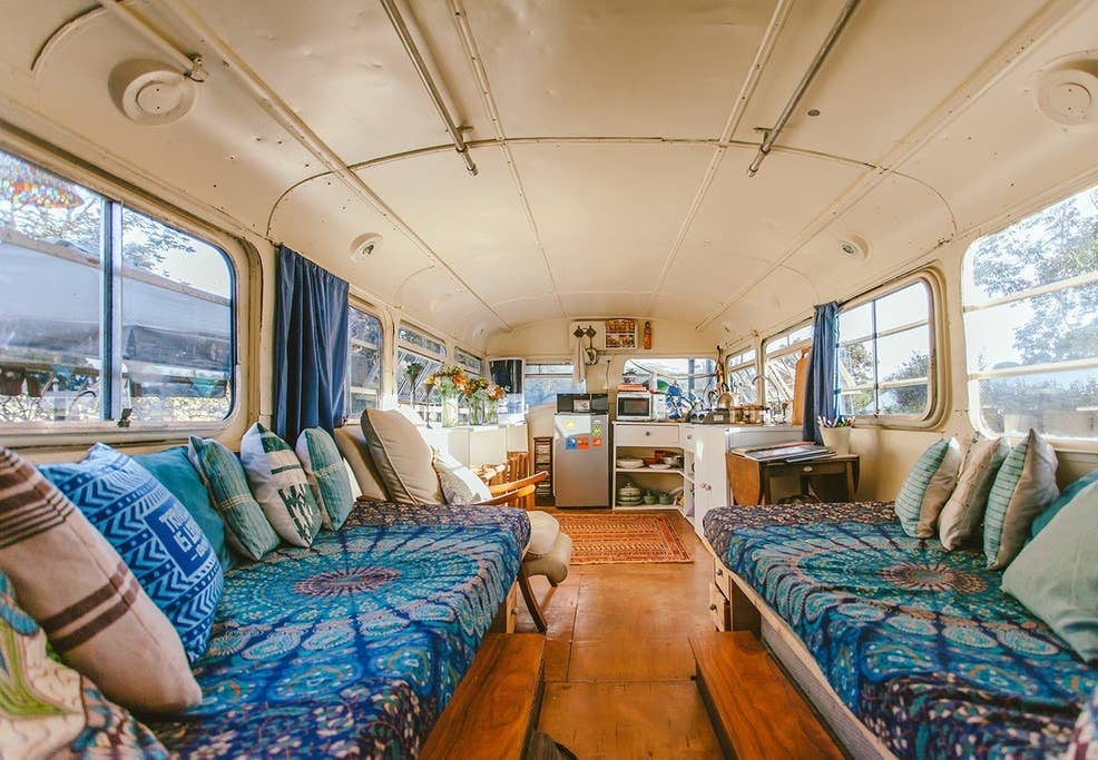 "If the Summer travel bug hasn't quite hit you yet, this charming double-decker bus on Airbnb will have you digging up your passport even before you process the cuteness of the colorfully embroidered throw pillows. Located in the lush suburbs of Nairobi, Kenya, the Brandy Bus, as it's known by guests, is surrounded by a gorgeous garden that even features a tennis court! The best part, though, is the interior, which feels so homey that just staring at the photos is enough to make me want to book an extended (read: permanent) stay. While staying in a bus might not be the first thought to pop in your head when you think vacation destinations, thoughtful touches throughout the bus truly make it seem like a home away from home — just look at all the flowers and the supercute knick-knacks! Described by past guests as a ""rough and tumble"" bus located in a relaxing oasis, the Brandy Bus gives off major glamping and road-trip vibes, ticking all the boxes on my Summer bucket list. The bus has four beds and one bathroom, comfortably accommodating six guests for $104 per night. See available booking dates for the Brandy Bus on the Airbnb website, and catch a glimpse at the charming getaway ahead. Related: You Know the Bali Tree House That's All Over Instagram? Yeah, It's Only $38 Per Night"