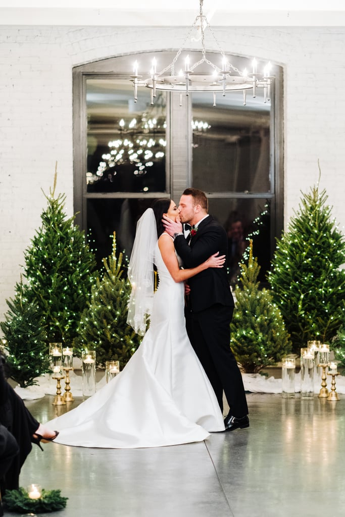 Last Christmas, Carlyn Bradarich and Patrick Schiller had the winter wedding of their dreams. The former Miss Iowa pageant winner and ex-NFL player celebrated their special day in Aurora, IL, at the industrial-chic event space Company 251 and surrounded by those closest to them. The winter wedding featured tasteful nods to the season with crimson-colored flowers, bright twinkly trees, and gorgeous green decor that filled the venue with subtle Christmas cheer. The bride was dressed in a modern white gown with a single string of pearls strung around her neck, along with an elegant veil that flowed down her back. Patrick sported a custom-made suit with the date of their wedding (12/7/2019) inscribed on the inside, as well as a sleek white suit that he changed into after the ceremony to match his new bride. Complete with cupcakes and Champagne, along with the traditional milk and cookies, every detail of their wedding was tastefully thought out, making this celebration a dream come true. From the bride's first steps down the aisle to the cutting of the cake, the love that these two share for each other could be felt by everyone in attendance. The wintry details perfectly captured the romance of the season, and made Carlyn and Patrick's wedding one to remember for Christmases to come. Take a look at the most moving moments (including a tearjerking first look) from this luxurious winter wedding, ahead.      Related:                                                                                                           This Rustic Christmas Tree Farm Wedding Shoot Was Inspired by a Taylor Swift Song
