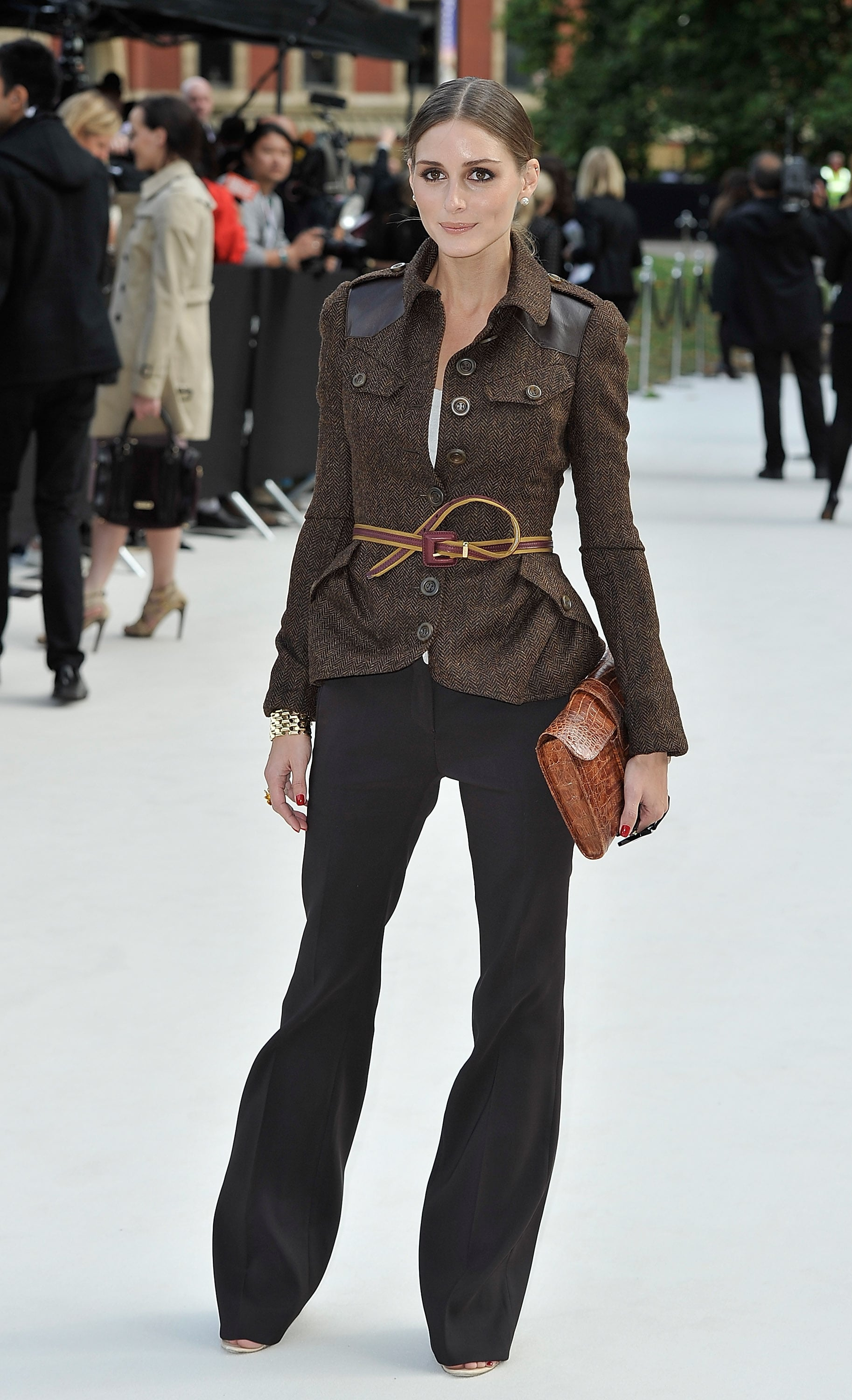 Olivia channeled Burberry's military vibe for the label's Spring show, outfitting a structured blazer with flared trousers and her signature skinny belt at the waist and an Hermès clutch in hand.