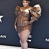 Lizzo absolutely stunned in this wood-print minidress, which she accessorized with a matching hat, boots, and nails. It's truly an ensemble.