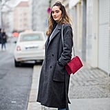 With Jeans, a Long Coat, and a Red Bag