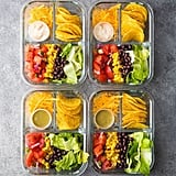 Vegetarian nacho bento box with black beans, corn, tomatoes, and lettuce.