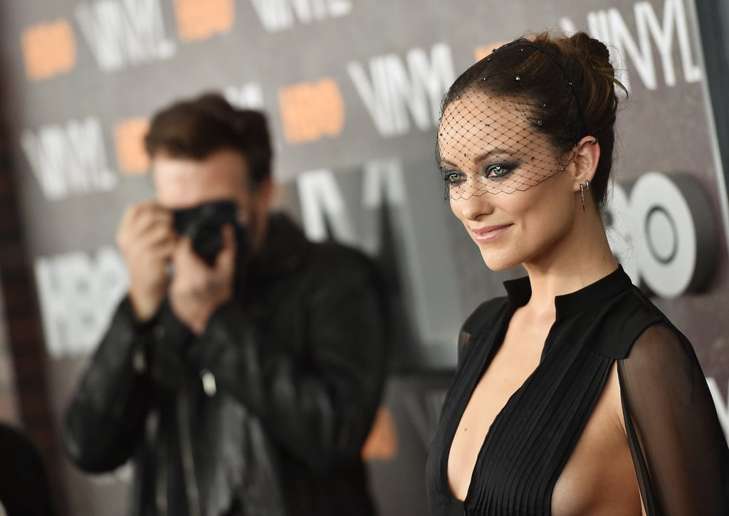 """Olivia Wilde steamed up the red carpet at the premiere of her new HBO series Vinyl in NYC on Friday night. The actress stunned in a low-cut black dress and a Jennifer Behr mesh veil as she posed for photos with costar Bobby Cannavale and legendary rocker Mick Jagger, who created the show along with famed director Martin Scorsese. Ray Ramano, Juno Temple, and Mick's 30-year-old son James Jagger also star in the series, which debuts on Feb. 14. On the red carpet, Olivia also had the support of her fiancé, Jason Sudeikis, who playfully snapped pictures of her along with all the other photographers.  Olivia and Jason recently brought their adorable antics to the Golden Globes last Sunday; the couple, who are parents to nearly 2-year-old son Otis, shared a hilarious Instagram snap of their middle fingers while on their way to the event, writing, """"Most parties that start at 3pm involve bouncy castles. Don't let us down, Hollywood."""" Keep reading to see Olivia and Jason on the red carpet, then check out all of their cutest relationship moments over the years."""