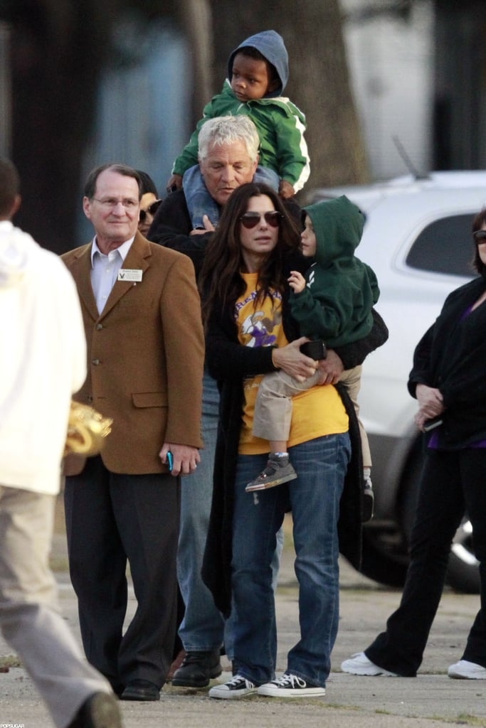 Sandra Bullock held Levi McConaughey as her son, Louis Bullock, got a ride on a friend's shoulders.