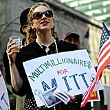 "This woman held a sign against presidential candidate Mitt Romney stating ""Multimillionaires for Mitt"" outside his campaign fundraiser in New York."
