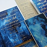 """All items in the gorgeous celestial suite were hand-painted with deep blue washes of ink and accented with gold foil text, more hand-painted shimmery spatter, and rhinestones. Instead of traditional table numbers on the day of, table placements can be represented by different constellations."" — Kristy Rice, Momental Designs"