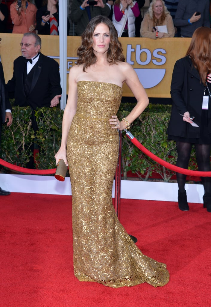 Jennifer Garner channelled her inner golden goddess in a lace and sequin Oscar de la Renta gown, chain link bracelet, and jewelled earrings.