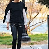 Olivia Palermo walked her dog in a pair of black leather pants with a cool double-zip detail. Yellow monogrammed loafers, a black cape sweater, a silky white blouse, and cat-eye sunglasses rounded out her chic NYC street style.
