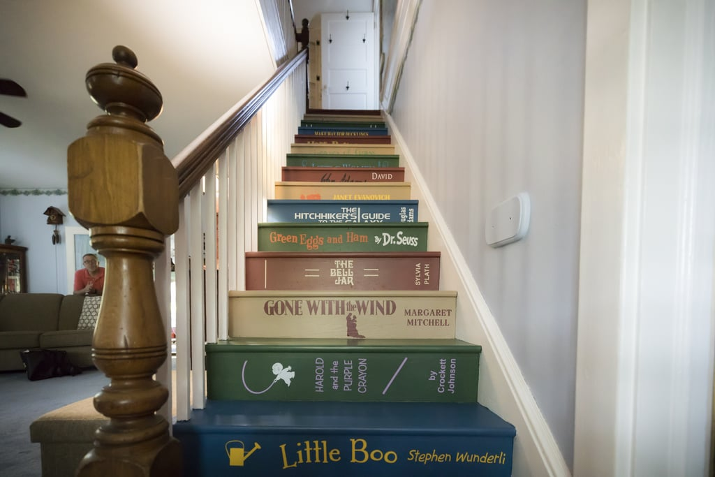 After three decades spent surrounded by books, librarian Bonnie Mendes wanted to express her love of reading in her home. She enlisted the help of her husband Jay to help her create a Pinterest-inspired book staircase in the couple's Massachusetts home. Jay started by heading to Lowe's for supplies and tips on how to remove the existing carpet from the stairs. Once that was done, he began painting and transforming their wooden staircase into a ascending stack of classic books, including classics like Little Women and Harry Potter, beloved by the couple and their now-grown children. The end result is a one-of-a-kind DIY feature — and conversation starter — sure to bring joy into their home for years to come. Take a look in the slideshow ahead.