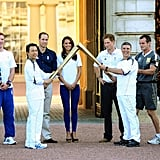 Prince William and Kate Middleton greeted the torch at Buckingham Palace on the eve of the Olympics.