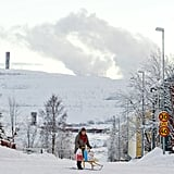 A woman rode her sled along a snowy road in Sweden.