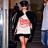 Wearing a graphic tee paired with a leather black cape and Moschino sunglasses.