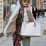 Olivia manages to master Autumn layering with a vest, scarf, and chunky knit.