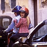 Hopping onto a scooter to tour Rome wearing a red striped blouse and jeans.