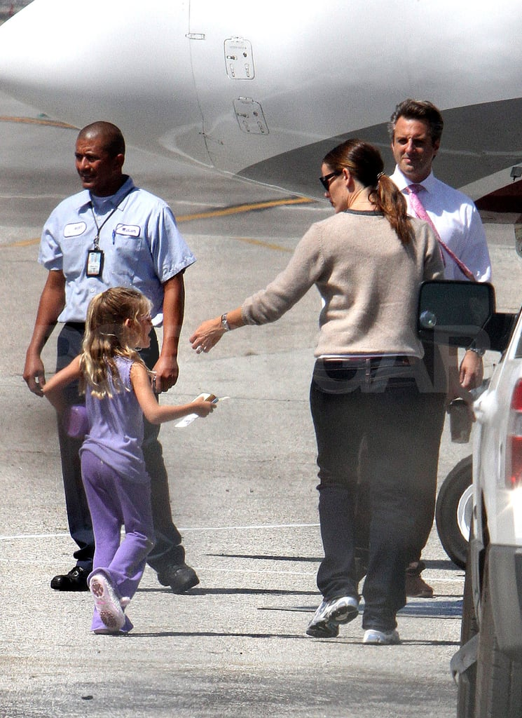 Jennifer Garner helps daughter Violet Affleck on to a private jet.