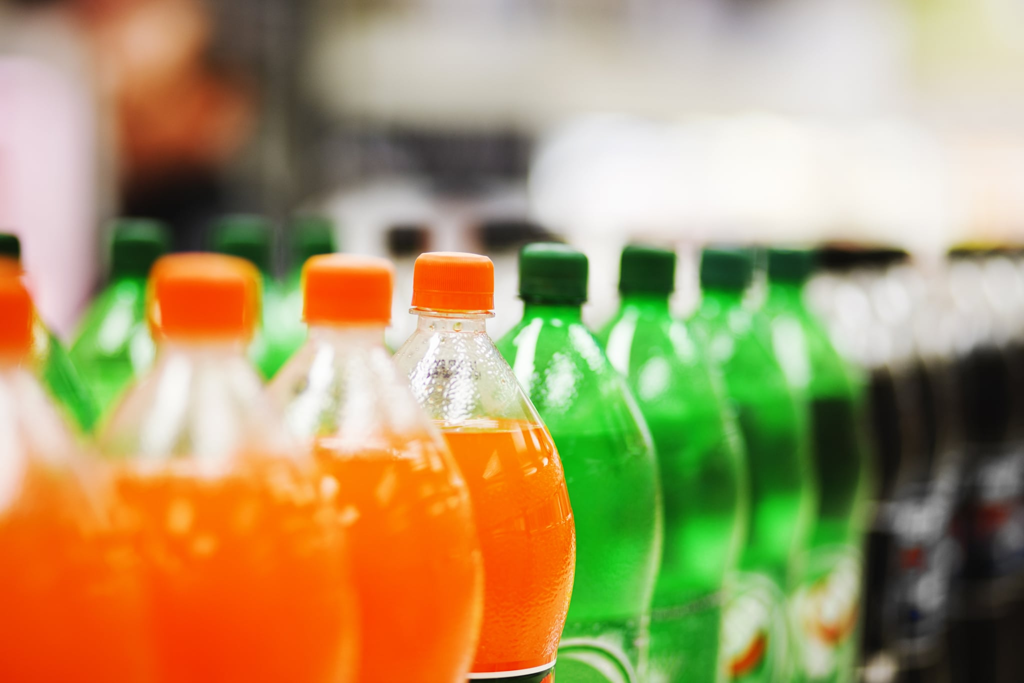 A long line of unbranded soda bottles in various flavours and colours, the focus on the centre of the line.