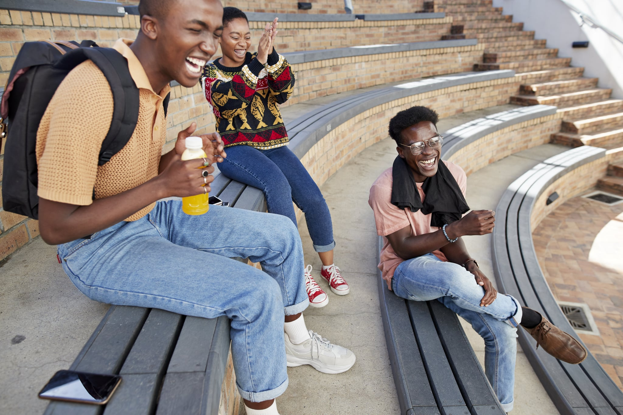 Cheerful young male and female friends enjoying on amphitheatre steps at university campus