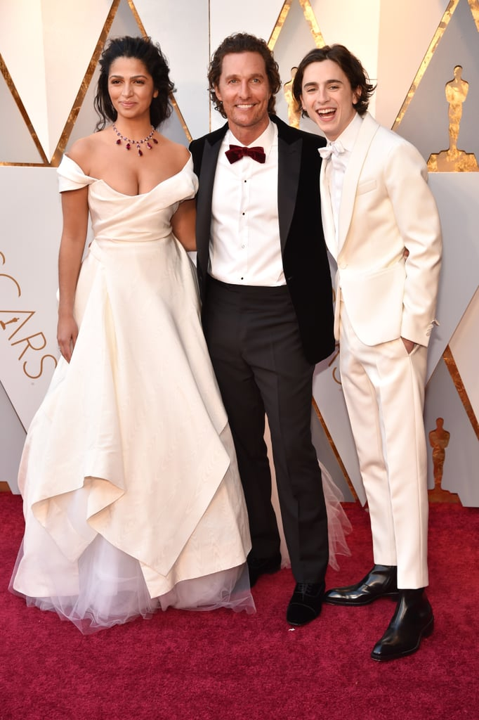 Timothée Chalamet has been adorably third-wheeling with costar Armie Hammer and his wife, Elizabeth Chambers, all award season long, but he decided to switch things up for the Oscars. On Sunday, the Call Me By Your Name star, who was nominated for best actor, looked too cute for words when he posed alongside his former Interstellar costar, Matthew McConaughey, and his wife Camila Alves.  Not only did Timothée match the model in his white tux, but he also shared a sweet moment as he laughed with Matthew in front of the cameras. Perhaps they were laughing over Timothée's spot-on impression of the Oscar winner.