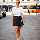 A t-shirt and white boots feel fresh with a dark miniskirt.