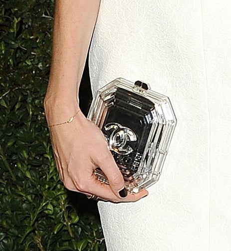 Poppy Delevingne paired her sequined dress with a clear Chanel-logo clutch.