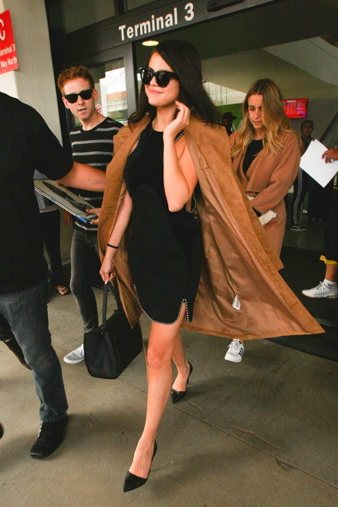 Fall staple: That same suede H&M coat. Selena wore it with: An Alexander Wang minidress, Céline sunglasses, a Louis Vuitton bag, and Giuseppe Zanotti pumps at LAX in October 2015.