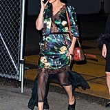 Selena Gomez arrived at Prada's resort show wearing a slinky floral silk by the brand, black mules, and a Coach monogram camera bag in 2018.